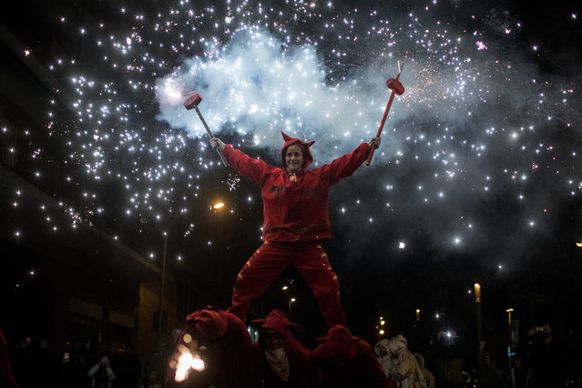 A woman dressed as a devil dances in the street under fire torches during the festival, Nit de Llufes on December 28, 2017 in Barcelona, Spain.  People dance and perform in the streets with fire torches to mark the Day of the Innocents. (Photo by Chris McGrath/Getty Images)