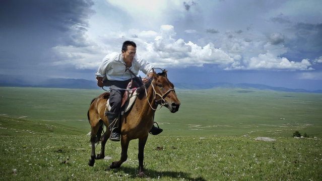Mongolia, 2009. Research scientist and National Geographic Emerging Explorer Albert Lin gallops across the steppes of northern Mongolia as he searches for Genghis Khan's tomb and other archaeological sites. (Photo by Mike Hennig