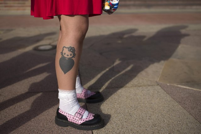 A woman with a Hello Kitty tattoo waits in line to attend the Hello Kitty Con, the first-ever Hello Kitty fan convention, held at the Geffen Contemporary at MOCA Thursday, October 30, 2014, in Los Angeles. The convention was held to honor the character's 40th birthday. (Photo by Jae C. Hong/AP Photo)