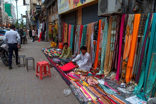 Vendors pack their fabrics at their roadside stall in front of closed shops in Karachi on July 25, 2020. (Photo by Rizwan Tabassum/AFP Photo)
