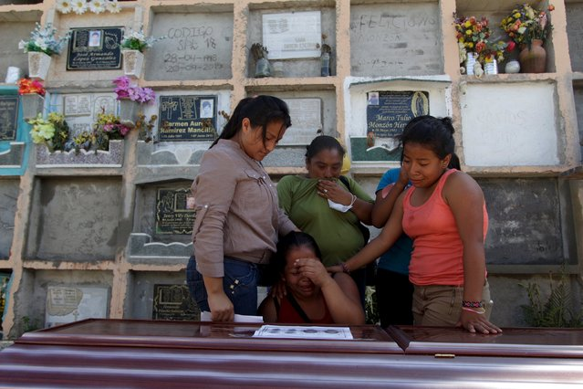 Relatives of a mudslide victim mourn over his coffin at a cemetery in Santa Catarina Pinula, on the outskirts of Guatemala City, October 6, 2015. (Photo by Jose Cabezas/Reuters)