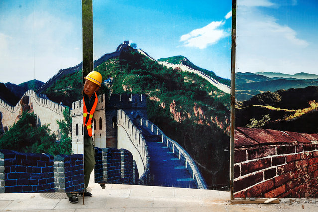A worker looks through the fence of a construction site that is decorated with pictures of the Great Wall at Badaling, north of Beijing, China, September 1, 2016. (Photo by Thomas Peter/Reuters)
