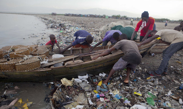 Fishermen remove their wooden boat from the sea as a precaution against Hurricane Irma, in the seaside slum of Port-au-Prince, Haiti, Wednesday, September 6, 2017. Heavy rain and 185-mph winds lashed the Virgin Islands and Puerto Rico's northeast coast Wednesday as Hurricane Irma roared through Caribbean islands. The northern parts of the Dominican Republic and Haiti could see 10 inches of rain. (Photo by Dieu Nalio Chery/AP Photo)
