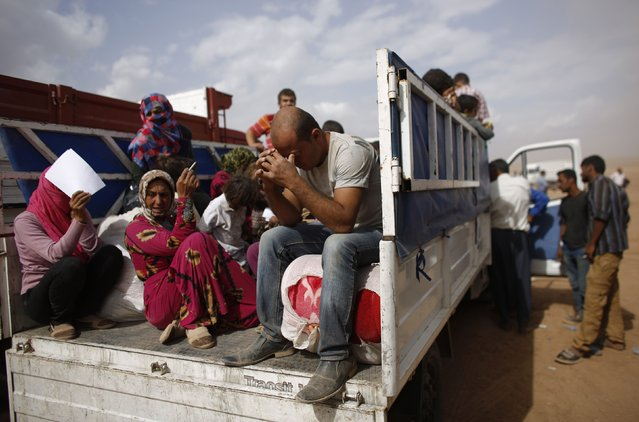 Syrian Kurdish refugees sit in a truck after crossing the Turkish-Syrian border near the southeastern town of Suruc in Sanliurfa province in this October 16, 2014 file photo. (Photo by Murad Sezer/Reuters)