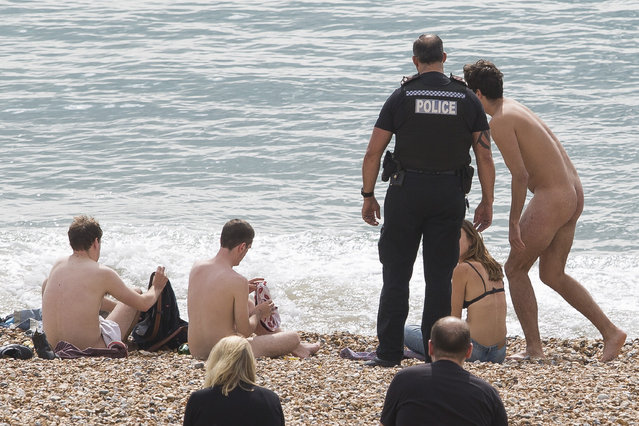 Police are called to deal with a group of people that are sunbathing naked on the beach in Brightonn, UK on September 187, 2016 away from the designated Nudist beach area while hundreds of people relax over lunchtime. (Photo by Hugo Michiels/London News Pictures)