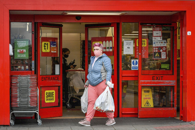 """A woman wearing a mask to protect against coronavirus, leaves a store, a day after the county borough of Caerphilly began a local lockdown following a """"significant rise"""" in coronavirus cases, in Caerphilly, South Wales, Wednesday, September 9, 2020. (Photo by Ben Birchall/PA Wire via AP Photo)"""