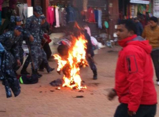 An exiled Tibetan monk sets himself on fire at Boudhanath Stupa in Kathmandu on February 13, 2013. A Tibetan monk doused himself in petrol in a Kathmandu restaurant and set himself on fire, marking the 100th self-immolation bid in a wave of protests against Chinese rule since 2009. Police in the Nepalese capital told AFP that the exile had burned himself in an eatery near Kathmandu's Boudhanath Stupa, one of the world's holiest Buddhist shrines, terrifying tourists who were having breakfast. (Photo by STR/AFP Photo)