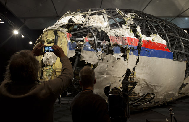 Journalists take images of part of the reconstructed forward section of the fuselage after the presentation of the Dutch Safety Board's final report into what caused Malaysia Airlines Flight 17 to break up high over Eastern Ukraine last year, killing all 298 people on board, during a press conference in Gilze-Rijen, central Netherlands, Tuesday, October 13, 2015. (Photo by Peter Dejong/AP Photo)