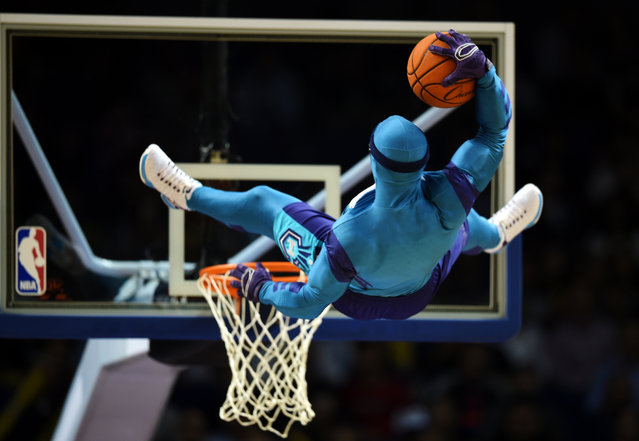 A man in a costume makes a stunt with a basketball before the 2015 NBA Global Games China pre-season basketball match, the Los Angeles Clippers vs Charlotte Hornets in Shanghai on October 14, 2015. (Photo by Johannes Eisele/AFP Photo)