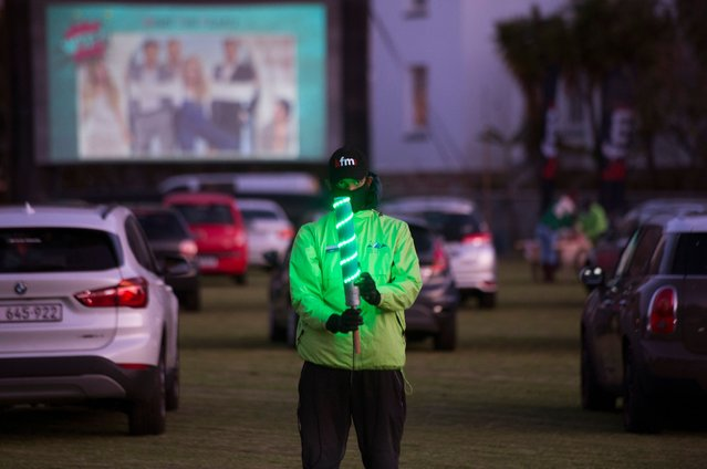 A park attendant helps people to park their cars in the right position at the Galileo drive-in, being held on a school sports field in Cape Town, on August 26, 2020. Drive-in cinemas have largely gone out of fashion, but with the Covid-19 pandemic affecting the country, this drive-in has been a way for people to safely go out and watch movies. (Photo by Rodger Bosch/AFP Photo)