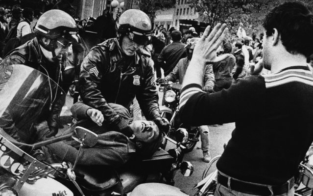 Helmeted Boston police officers work to restrain an unidentified man at Boston's City Hall Plaza on October 16, 1982 as an onlooker holds up his hands after demonstrators clashed with police during a Ku Klux Klan rally. (Photo by Bill Polo/AP Photo)