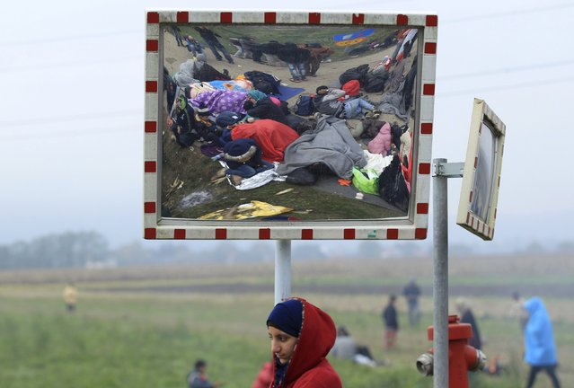 A girl looks on as resting migrants are seen in a street mirror after crossing the border from Croatia in Rigonce, Slovenia October 21, 2015. The Slovenian parliament passed legislation early on Wednesday that will give the army more power to help police guarding the state border as thousands of migrants flood into the country from Croatia after Hungary sealed off its border. (Photo by Antonio Bronic/Reuters)