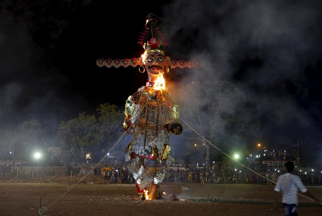 People watch as an effigy of demon king Ravana burns during the Hindu festival of Dussehra in Ahmedabad, India, October 22, 2015. (Photo by Amit Dave/Reuters)