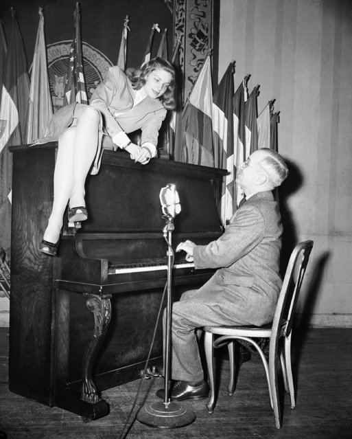 Vice President Harry S. Truman plays the piano as the new movie star Lauren Bacall, perched on the instrument, looks on, during her appearance at the National Press Club canteen in Washington, D.C., on February 10, 1945. (Photo by AP Photo)
