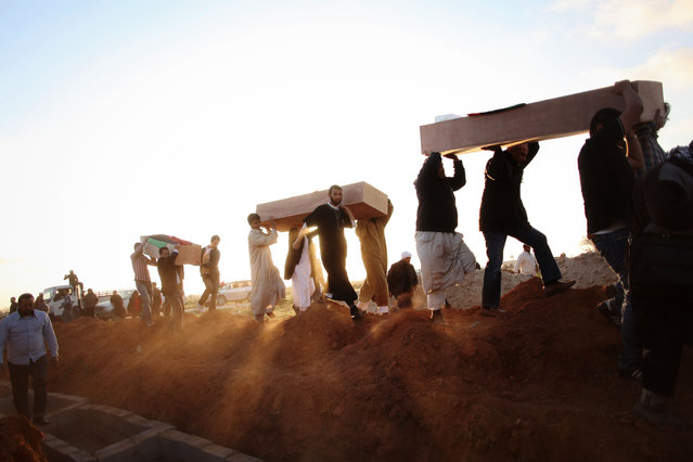 Libyan men carry coffins of victims, discovered in a mass grave, at a funeral in Benghazi, Libya, Monday, March 5, 2012. (Photo by Manu Brabo/AP Photo)