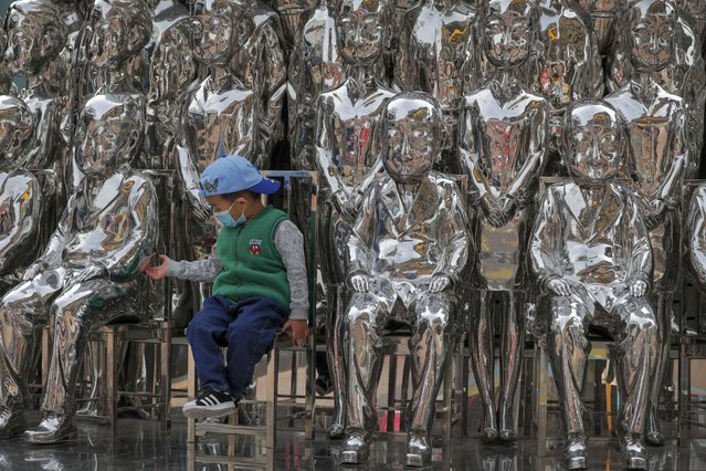 A child wearing a face mask to help curb the spread of the coronavirus tries to hold a statue's hand as he sits in an art installation on display at a shopping mall in Beijing, Sunday, October 11, 2020. Even though the spread of COVID-19 has been all but eradicated in China, the pandemic is still surging across the globe with ever rising death toll. (Photo by Andy Wong/AP Photo)
