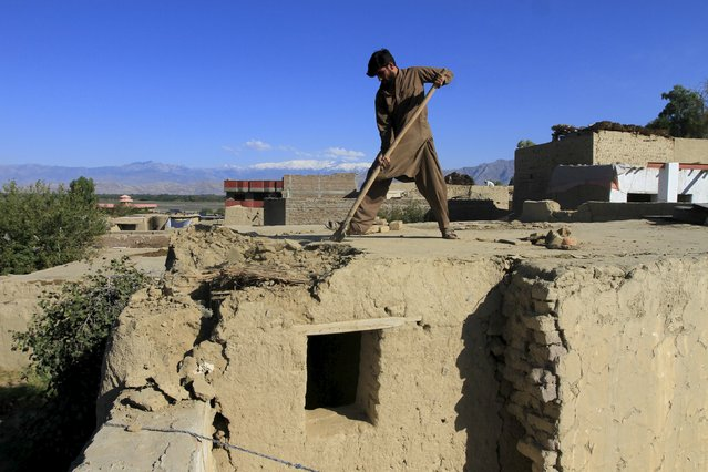 A man clears rubble from the roof of his house after an earthquake, in Behsud district of Jalalabad province, Afghanistan October 27, 2015. (Photo by Reuters/Parwiz)