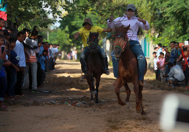 Men ride horses during the Pchum Ben festival, in Vihear Sour village in Kandal province, Cambodia, October 1, 2016. (Photo by Samrang Pring/Reuters)