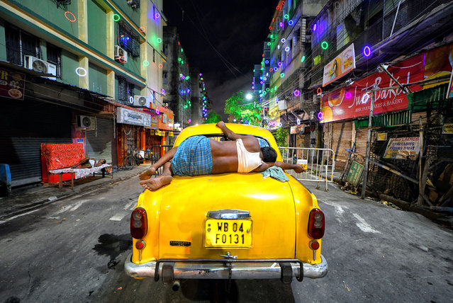 A taxi driver seen sleeping on his taxi in the middle of a decorated street during the Durga Puja Festival in Kolkata, India on October 22, 2020. (Photo by Avishek Das/SOPA Images/Rex Features/Shutterstock)