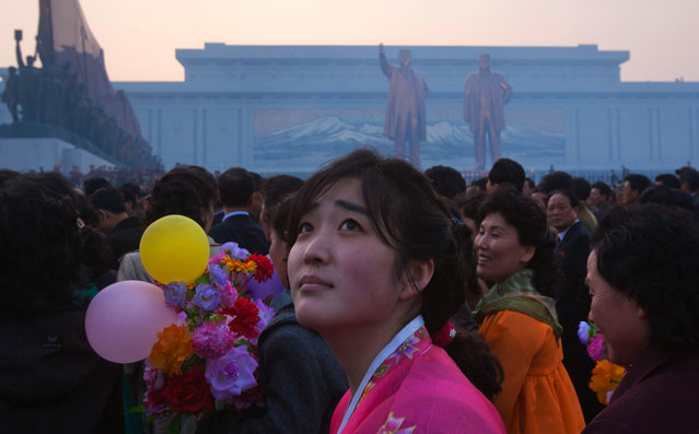 A North Korean woman looks up at balloons overhead at the end of an unveiling ceremony for statues of the late leaders Kim Il Sung and Kim Jong Il in Pyongyang, on April 13, 2012. (Photo by David Guttenfelder/AP Photo)