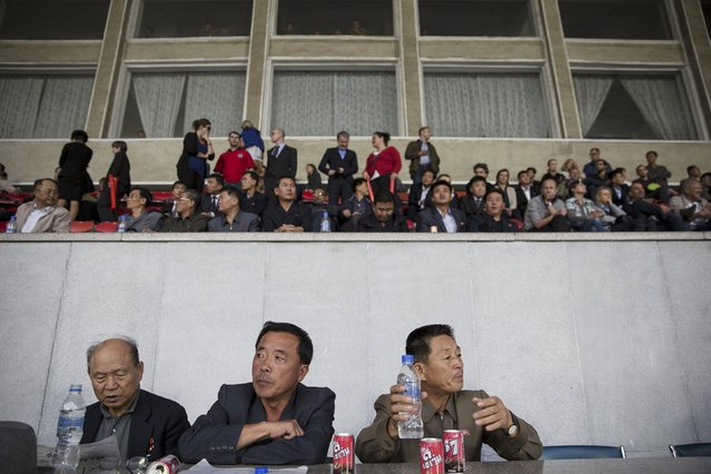 Locals and foreigners watch a football match from the VIP section of the Kim Il Sung Stadium in Pyongyang October 8, 2015. (Photo by Damir Sagolj/Reuters)