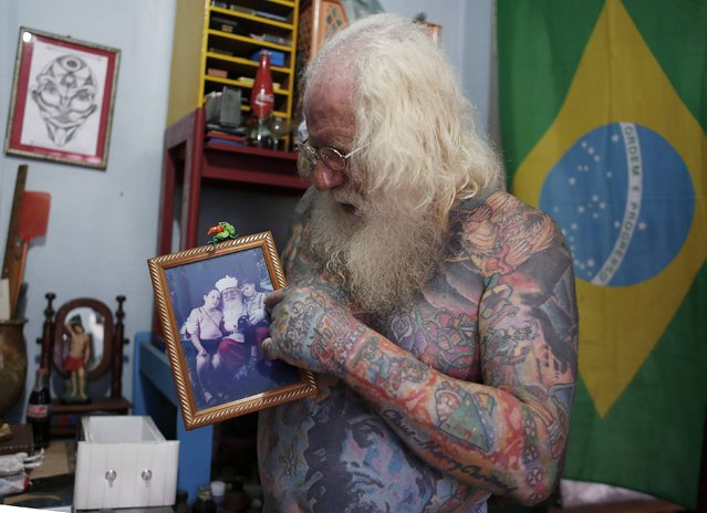 Vitor Martins shows a photo of himself, dressed as Santa Claus with his son and daughter, at his house, before a performance with children in Sao Caetano do Sul's town square, near Sao Paulo, December 7, 2014. (Photo by Nacho Doce/Reuters)