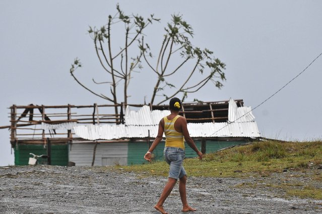 A woman walks past damaged housing in the Carbonera community of Guantanamo, Cuba following Hurricane Matthew, October 5, 2016. The storm slammed into Haiti and Cuba as a Category Four hurricane on October 4, 2016 but has since been downgraded to three, on a scale of five, by the US National Hurricane Center (NHC).  Its winds were howling at 115 miles per hour (185 kilometers per hour). (Photo by Yamil Lage/AFP Photo)
