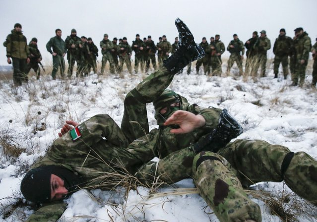 "Pro-Russian separatists from the Chechen ""Death"" battalion take part in a training exercise in the territory controlled by the self-proclaimed Donetsk People's Republic, eastern Ukraine, December 8, 2014. Chanting ""Allahu Akbar"" (God is greatest), dozens of armed men in camouflage uniforms from Russia's republic of Chechnya train in snow in a camp in the rebel-held east Ukraine. (Photo by Maxim Shemetov/Reuters)"