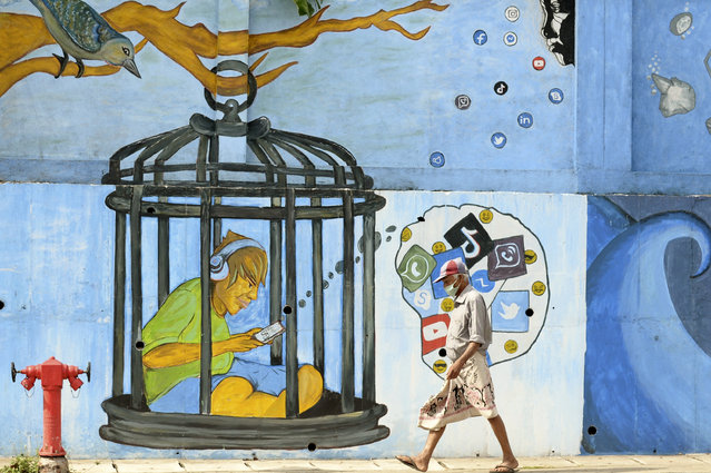 A man wearing a facemask as a preventative measure against the Covid-19 coronavirus walks past a mural in Colombo on October 19, 2020. (Photo by Lakruwan Wanniarachchi/AFP Photo)