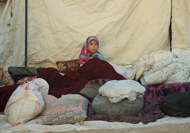 An Afghan girl with her family waits for help from the government and aid organizations in Takhar, Afghanistan October 11, 2016, after fleeing their homes in neighboring Kunduz, which has been the scene of fighting between Taliban militants and government troops. (Photo by Nasir Wakif/Reuters)