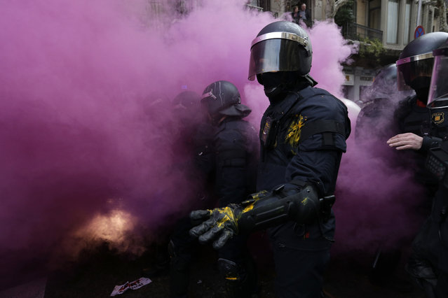 Catalan Mossos d'Esquadra regional police officers stand amid smoke from a smoke bomb during clashes with pro-independence supporters trying to reach the Spanish government office in Barcelona, Spain, Sunday, March 25, 2018. Grassroots groups both for and against Catalan secession called for protests Sunday in Barcelona after Carles Puigdemont, the fugitive ex-leader of Catalonia and ardent separatist, was arrested Sunday by German police on an international warrant. (Photo by Emilio Morenatti/AP Photo)