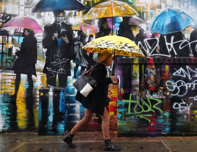A woman with an umbrella walking past street art in Camden, London on October 21, 2020. Weather warnings have been issued as Storm Barbara is expected to bring gale force winds and heavy showers to southern parts of the UK. (Photo by Yui Mok/PA Images via Getty Images)