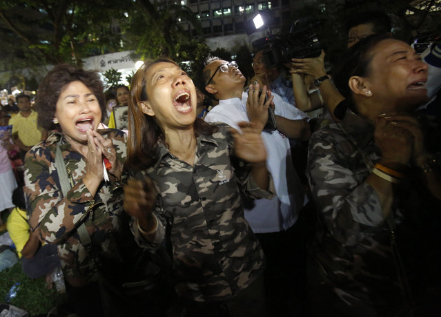Thai people cry after Royal Palace's announcement outside Siriraj Hospital where King Bhumibol Adulyadej was being treated, in Bangkok, Thailand, Thursday, October 13, 2016. (Photo by Sakchai Lalit/AP Photo)
