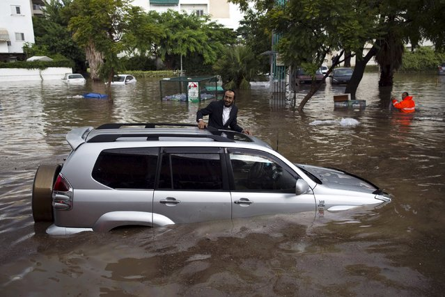 A motorist climbs out of his vehicle after getting stuck on a flooded street in the southern city of Ashkelon, Israel, November 9, 2015. (Photo by Amir Cohen/Reuters)