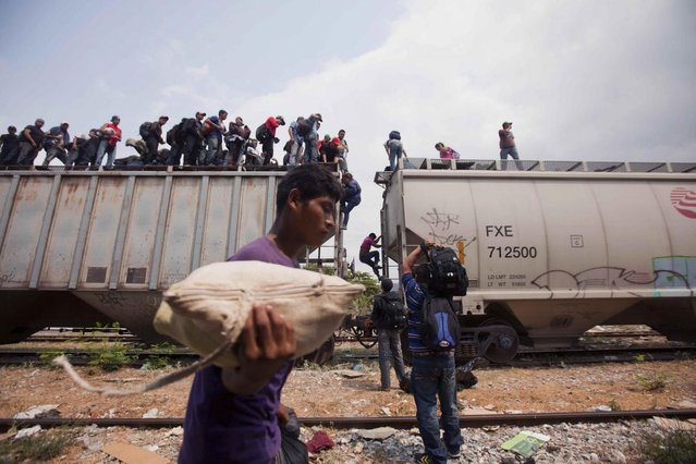 Migrants coming from Central America climb off a train during their journey toward the U.S.-Mexico border in Ixtepec, Mexico, Monday, April 29, 2013. Migrants crossing Mexico to get to the U.S. have increasingly become targets of criminal gangs who kidnap them to obtain ransom money. (Photo by Eduardo Verdugo/AP Photo)