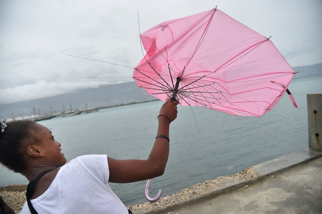 A girl tries to repair her umbrella that was broken by the wind, in the commune of Cite Soleil, in the Haitian capital Port-au-Prince, on October 3, 2016. Hurricane Matthew took aim at densely populated Haiti and Jamaica on Monday, packing winds that could sweep away flimsy buildings and bringing torrential rain that could trigger deadly landslides and floods. As the powerful storm churned north, officials in both countries scrambled to protect buildings and move people out of danger zones to shelters. (Photo by Hector Retamal/AFP Photo)