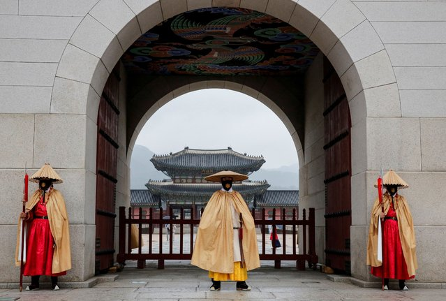 Workers wearing traditional attire wear masks to prevent the spread of the coronavirus disease (COVID-19) during the daily re-enactment of the changing of the Royal Guards at Gyeongbok Palace in central Seoul, South Korea, November 19, 2020. (Photo by Heo Ran/Reuters)