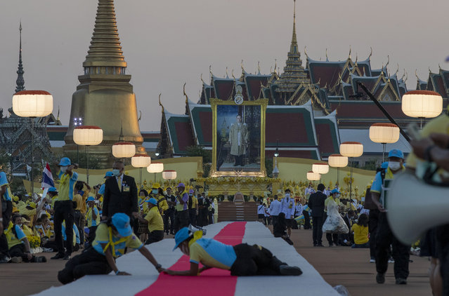 Officials adjust a carpet as late King Bhumibol Adulyadej's images is displayed in the background ahead of the arrival of King Maha Vajiralongkorn and Queen Suthida to participate in a candle lighting ceremony to mark birth anniversary of late King Bhumibol Adulyadej at Sanam Luang ceremonial ground in Bangkok, Thailand, Saturday, December 5, 2020. (Photo by Gemunu Amarasinghe/AP Photo)