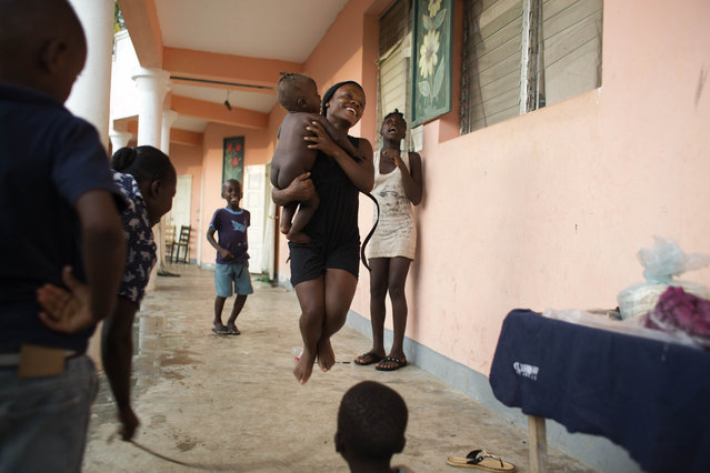 A youth jumps rope, while holding a baby, at a school where people have taken refuge after losing their homes to Hurricane Matthew in the village of Mersan, located in Camp-Perrin, a district of Les Cayes, Haiti, Sunday, October 16, 2016. Aid workers who specialize in working with children in crisis say they fear kids will struggle with emotional aftershocks of the violent storm. (Photo by Dieu Nalio Chery/AP Photo)