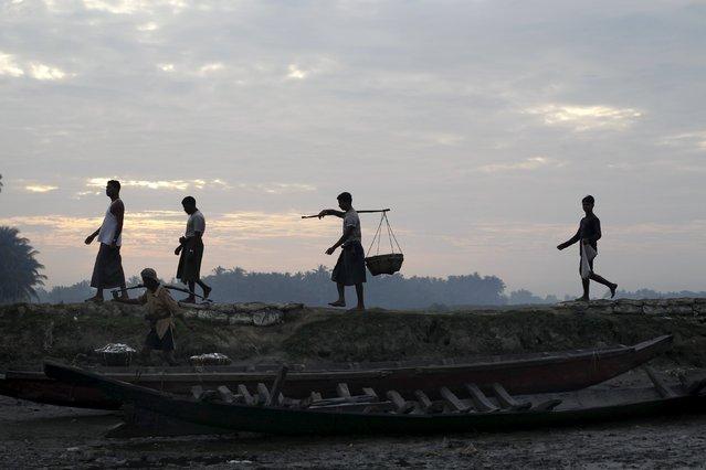 Muslim Rohingya fishermen walk by the port at a refugee camp outside Sittwe October 29, 2015. (Photo by Soe Zeya Tun/Reuters)