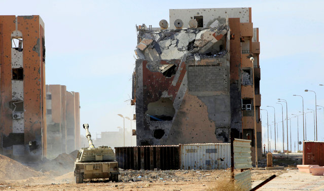 A military vehicle for Libyan forces allied with the U.N.-backed government is stationed in front of ruined buildings at the eastern frontline of fighting with Islamic State militants, in Sirte's neighbourhood 650, Libya, October 21, 2016. (Photo by Ismail Zitouny/Reuters)