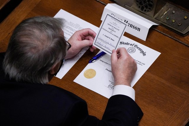 Democratic Electoral College elector Steve Henson looks at his signed vote for Joe Biden for President of the United States in the Georgia State Senate chambers in the Georgia State Capitol building in Atlanta, Georgia, U.S., December 14, 2020. (Photo by Elijah Nouvelage/Reuters)