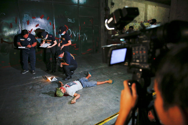 Investigators take notes next to the body of a man killed in a shootout with police in Manila, Philippines early October 21, 2016. According to the police, sachets containing substance believed to be drug shabu (Metamphetamine Hydrochloride) were found in the killed man's pockets. (Photo by Damir Sagolj/Reuters)
