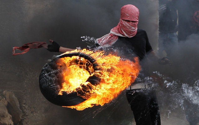 "A Palestinian sets fire to a tyre during clashes between hundreds of Palestinians and Israeli soldiers outside the Ofer prison after a march marking the 65th Nakba day or ""Day of Catastrophe"" in Betunia near the West Bank city of Ramallah, on May 15, 2013. (Photo by Abbas Momani/AFP Photo)"
