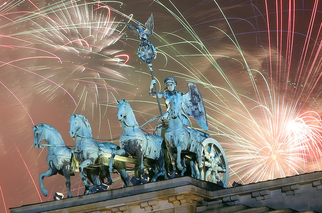 Fireworks explode behind the Quadriga statue on top of the Brandenburg Gate shortly after midnight on January 1, 2015 in Berlin, Germany. Tens of thousands of revelers gathered in the city center to celebrate New Year's Eve. (Photo by Adam Berry/Getty Images)