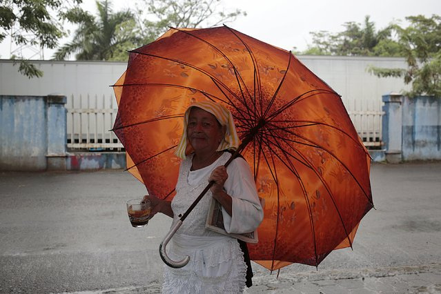 A woman holds an umbrella as she walks outside the customs building at the border between Nicaragua and Costa Rica November 16, 2015. (Photo by Oswaldo Rivas/Reuters)