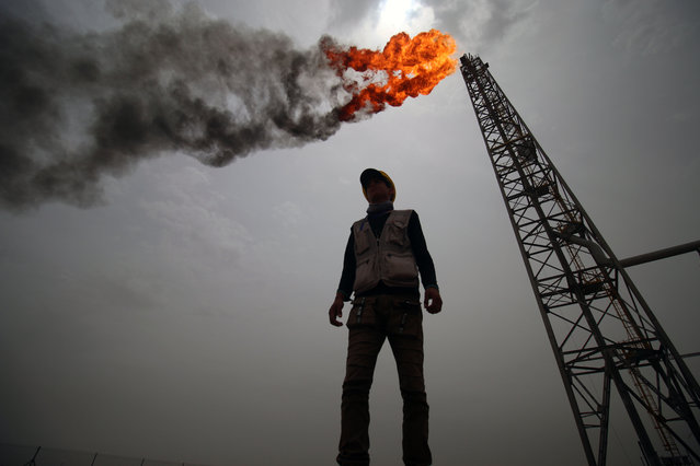 An employee stands at the Hammar Mushrif new Degassing Station Facilities site inside the Zubair oil and gas field, north of the southern Iraqi province of Basra on May 9, 2018. (Photo by Haidar Mohammed Ali/AFP Photo)