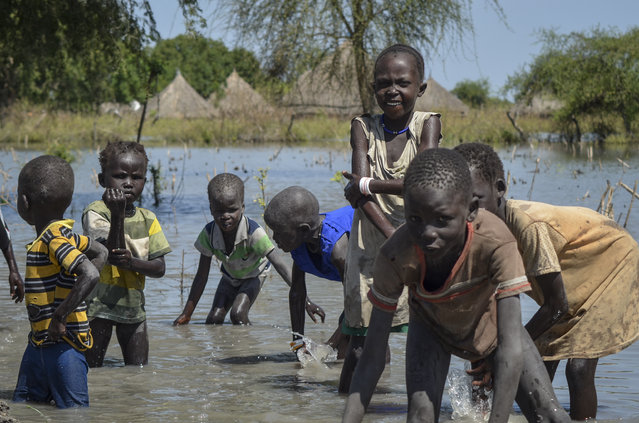 Children wash themselves in muddy floodwaters in the village of Wang Chot, Old Fangak county, Jonglei state, South Sudan Thursday, November 26, 2020. One county in South Sudan is likely in famine and tens of thousands of people in five other counties are on the brink of starvation, according to a new report released Friday, Dec. 11, 2020 by international food security experts. (Photo by Maura Ajak/AP Photo)