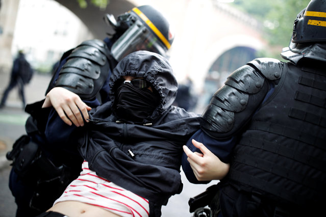 French riot police apprehend a masked and hooded protester after clashes at a demonstration during a national day of strikes by public sector workers, in Paris, France on May 22, 2018. (Photo by Christian Hartmann/Reuters)