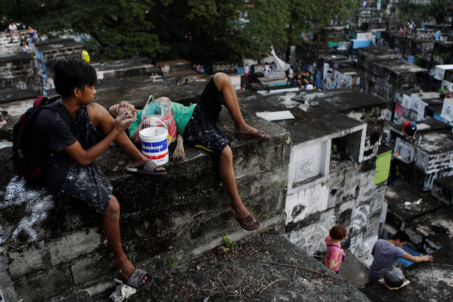 Cemetery workers take a rest atop apartment-style tombs as Filipinos visit the graves of their deceased loved ones to commemorate All Saints Day, at Barangka public cemetery in Marikina city, Metro Manila, Philippines November 1, 2016. (Photo by Czar Dancel/Reuters)